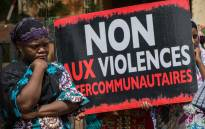 FILE: Women hold a placard with an inscription 'No to intercommunity violents' during a demonstration on 22 June 2019 in front of the Ouagadougou courthouse to demand 'truth and justice' for the victims of Yirgou, a locality in northern Burkina Faso where retaliation against the Fulani community, after a terrorist attack, left 49 dead on 1 January 2019. Picture: AFP