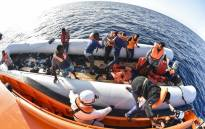 FILE: Men evacuate a rubber boat with the help of the crew of the Topaz Responder ship run by Maltese NGO Moas and the Italian Red Cross during a rescue operation of migrants and refugees on 3 November 2016 off the Libyan coast in the Mediterranean Sea. Picture: AFP.