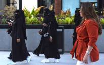 FILE: Saudi human resources professional Mashael al-Jaloud, 33, walks in western clothes past women wearing niqab, an Islamic dress-code for women, at a commercial area in the Saudi capital Riyadh on 3 September 2019. Picture: AFP.