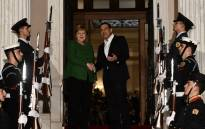 Greece's Prime Minister Alexis Tsipras (R) shakes hands with German Chancellor Angela Merkel as she arrives in Athens on 10 January 2019. Picture: AFP