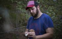 Justin Williams cleans a porcini mushroom he picked in Newlands Forest. Picture: Aletta Harrison/EWN