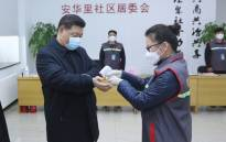 FILE: This photo released on 10 February 2020 by China's Xinhua News Agency shows Chinese President Xi Jinping (L) wearing a protective facemask as a health official (R) checks his body temperature during an inspection of the novel coronavirus pneumonia prevention and control work at the Anhuali Community in Beijing. Picture: AFP.