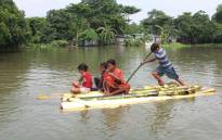 FILE: Indian residents use a makeshift raft to cross a flooded locality after the River Atreyee overflowed following heavy monsoon rains at Chakvrigu near Balurghat in South Dinajpur district of India's West Bengal state in July 2019. Picture: AFP