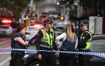 Police work at the crime scene following a stabbing incident in Melbourne on 9 November 2018. One person was killed and two others injured in a rush-hour stabbing incident in Melbourne's bustling central business district, prompting police to shoot a knife-wielding suspect near a burning vehicle. Picture: AFP.