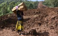 A woman carries a rolled-up mattress at a landslide site in Shisakali village of Bududa district, eastern Uganda, on 6 June 2019. Picture: AFP