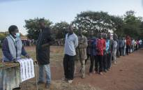 An electoral official (L) checks the voters' roll while people queue to vote at the Malembo polling station during the presidential elections in Lilongwe on 23 June 2020. Picture: AFP