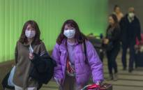 FILE: Travelers arrive at LAX Tom Bradley International Terminal wearing medical masks for protection against the novel coronavirus outbreak on 2 February 2020 in Los Angeles, California. Picture: AFP
