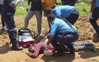Paramedics tend to a person who was injured by police during protests in Mbabane on 20 October 2021. Picture: AFP