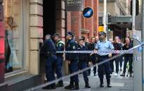 Police investigate the area around a crime scene after a man stabbed a woman and attempted to stab others in central Sydney on 13 August 2019, before being pinned down by members of the public and detained by police. Picture: AFP