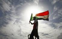 FILE: A Sudanese man carries the country's flag during a protest. Picture: AFP