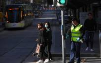 FILE: A cleaner (R) wipes down a pole in Melbourne's central business district on 17 June 2020, as more Australians return to the city centre with a relaxing of the COVID-19 coronavirus rules. Picture: AFP