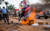 A supporter of Ugandan musician turned politician Robert Kyagulanyi, also known as Bobi Wine, carries his poster as they protest on a street against the arrest of Kyagulanyi during his presidential rally in Kampala, Uganda, on 18 November 2020. Picture: AFP
