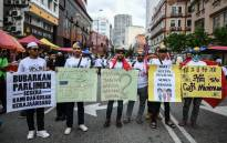 Protesters display placards during a rally organised by Muslim politicians against the signing of the UN anti-discrimination convention (ICERD) at Merdeka Square in Kuala Lumpur on 8 December 2018. Picture: AFP.