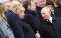 Russian President Vladimir Putin (R), talks with German Chancellor Angela Merkel (C) and US President Donald Trump as they attend a ceremony at the Arc de Triomphe in Paris on 11 November 2018 as part of commemorations marking the 100th anniversary of the 11 November 1918 armistice, ending World War I. Picture: AFP