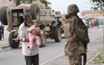 A grandfather holds his baby up to greet a soldier as SAPS and members of the SANDF conduct crime-fighting operations in Manenberg. Picture: Bertram Malgas/EWN