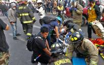 Firefighters assist demonstrators after a car ran over people protesting against the government of Sebastian Pinera in Antofagasta, Chile on 21 November 2019. Picture: AFP