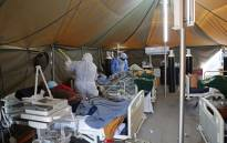 FILE: A professional healthcare worker wearing personal protective equipment (PPE) treats a patient in a tent dedicated to the treatment of possible COVID-19 coronavirus patients, while another cleans the ward at the Tshwane District Hospital in Pretoria on 10 July 2020. Picture: AFP