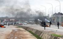 Policemen shoot canister of tear gas to disperse people during a demonstration and attacks against South African-owned shops in Abuja, on 4 September 2019. Picture: AFP