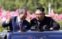 North Korean leader Kim Jong Un (R) listens to South Korean President Moon Jae-in (L) in an open-topped vehicle as they drive through Pyongyang on 18 September 2018. Picture: AFP