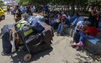 Venezuelans rest after crossing the border from San Antonio del Tachira in Venezuela into Cucuta, in Norte de Santander Department, Colombia, through the Simon Bolivar international bridge on 19 August, 2018. Picture: AFP.