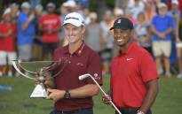 Justin Rose holds the FedEx Cup and Tiger Woods holds the Calamity Jane a replica of Bobby Jones putter after winning the Tour Championship golf tournament. Picture: @playofffinale/Twitter.
