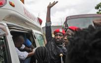 Ugandan singer-turned-politician Robert Kyagulanyi (C) reacts as he gets into an ambulance after being released on bail at the High Court in Gulu on 27 August 2018. Picture: AFP.