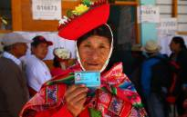 A woman shows her identity card at a polling station in Ollantaytambo, a town located in what is known as the Sacred Valley of the Incas in the province of Urubamba, Cusco region, in southern Peru, as the country votes on President Martin Vizcarra's constitutional reforms aimed at eradicating corruption, on 9 December 2018. Picture: AFP