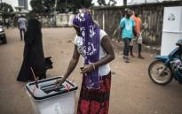 A voter casts her ballot at a voting booth in the popular opposition neighbourhood of Bambeto during presidential elections in Conakry, Guinea on 18 October 2020. Picture: AFP