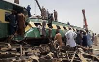 Security personnel and onlookers stand at the site of a train accident in Daharki area of the northern Sindh province on 7 June 2021, as at least 34 people were killed and dozens injured when a packed Pakistani inter-city train ploughed into another express that had derailed earlier, officials said. Picture: Shahid Ali/AFP
