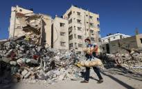 A Palestinian bakery worker holds bags of bread past the ruins of a building destroyed during the recent Israeli bombings, in Gaza City on 27 May 2021. Picture: Mohammed Abed/AFP