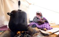 A displaced woman from the Libyan town of Tawergha, 260km east of the Libyan capital Tripoli, prepares food on 8 February 2018 at a temporary camp, 20kms from Tawergha, after they were denied entry to their hometown. Picture: AFP.