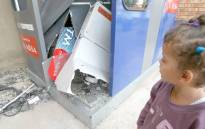 FILE PICTURE: A young girl looks at the remains of an ATM, after robbers bombed it. Picture: SAPA