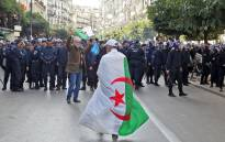 A man draped in an Algerian national flag walks towards security forces as they surround protesters staging an anti-government demonstration in the capital Algiers on 12 December 2019 on the day of the presidential election. Picture: AFP