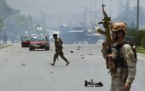 Afghan security personnel take position at the site of an attack in front of the parliament building in Kabul on 22 June 2015. Picture: AFP.