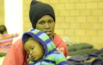 A woman and her baby sit on a matress in the Nomzamo Community Hall on 4 June 2014 following their forced eviction. Picture: Aletta Gardner/EWN