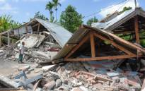 FILE: An Indonesian man examines the remains of houses, after a 6.4 magnitude earthquake struck, in Lombok on 29 July, 2018. Picture: AFP.