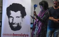 A journalist stands in front of a poster featuring jailed businessman and philanthropist Osman Kavala during a press conference of his lawyers on 31 October 2018. Picture: AFP.