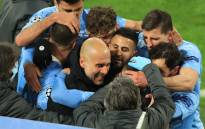 Manchester City midfielder Phil Foden (C, hidden) celebrates scoring the winning goal with his teammates and manager Pep Guardiola during the UEFA Champions League quarter-final second leg football match between BVB Borussia Dortmund and Manchester City in Dortmund, western Germany, on 14 April 2021. Picture: Wolfgang Rattay/AFP