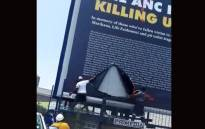 Two men tear the DA's billboard. Picture: @Xondo712/Twitter.
