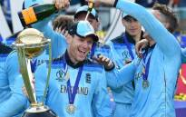 England's captain Eoin Morgan is covered in champagne as he poses with the World Cup trophy as England's players celebrate their win after the 2019 Cricket World Cup final between England and New Zealand at Lord's Cricket Ground in London on 14 July 2019. Picture: AFP