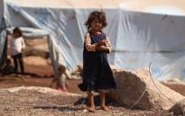 A displaced Syrian girl who fled from regime raids stands outside her tent in a camp in Kafr Lusin near the border with Turkey in the northern part of Syria's rebel-held Idlib province on 9 September 2018. Picture: AFP.