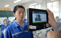File: A teacher uses a machine which employs both fingerprint and facial recognition technology to check the identification of a student before a simulated college entrance exam in Handan in China's northern Hebei province on June 6, 2017. Picture: AFP.
