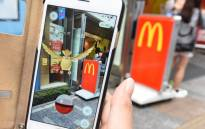 A woman plays Nintendo's Pokemon Go game on her mobile phone in front of a McDonald's restaurant at Akihabara shopping district in Tokyo on 22 July 2016. Picture: AFP.