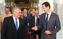 FILE: This handout picture released by the Syrian Presidency Facebook page on 25 July 2018, shows President Bashar al-Assad (R) welcoming Russian President's Special Envoy to Syria Alexander Lavrentiev (L) in Damascus. Picture: AFP