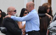 Reeva Steenkamp's father (left) is consoled at his daughter's cremation.