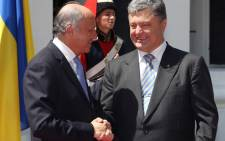 FILE: French minister of Foreign Affairs Laurent Fabius (L) shakes hands with Ukrainian President Petro Poroshenko, upon the French diplomatic delegation's arrival in Kiev, on 7 June, 2014. Picture: AFP.