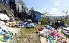 A man stands outside his home with his belongings on 17 March, 2015 in a shantytown of Port Villa after Severe Tropical Cyclone Pam hit the Pacific nation of Vanuatu on 13 March. Picture: AFP.