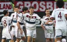 Bayern's players celebrate teammate Thomas Mueller scoring the 3-0 during the German first division Bundesliga football match Eintracht Frankfurt vs FC Bayern Munich. Picture: AFP.