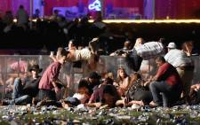 People scramble for shelter at the Route 91 Harvest country music festival after a man opened fire on 1 October 2017 in Las Vegas, Nevada. Picture: AFP.