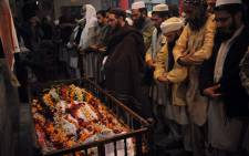 Pakistani mourners pray during the funeral of a victim following an attack by Taliban gunmen on a school in Peshawar on 16 December, 2014. Picture: AFP.